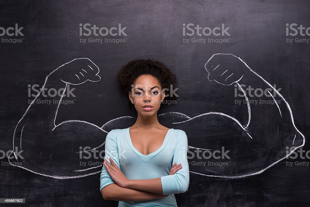Serious afro-american woman with painted muscular arms on chalkboard stock photo