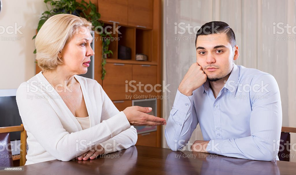 Serious aged female and young boyfriend stock photo