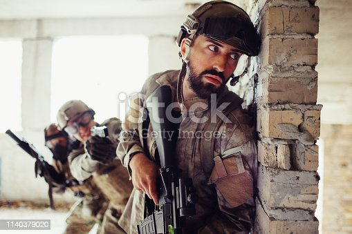 istock Serious and careful man is leaning to wall. He is aiting. There are his partners behind him. Guys are waiting fot the perfect time to attack enemy. 1140379020