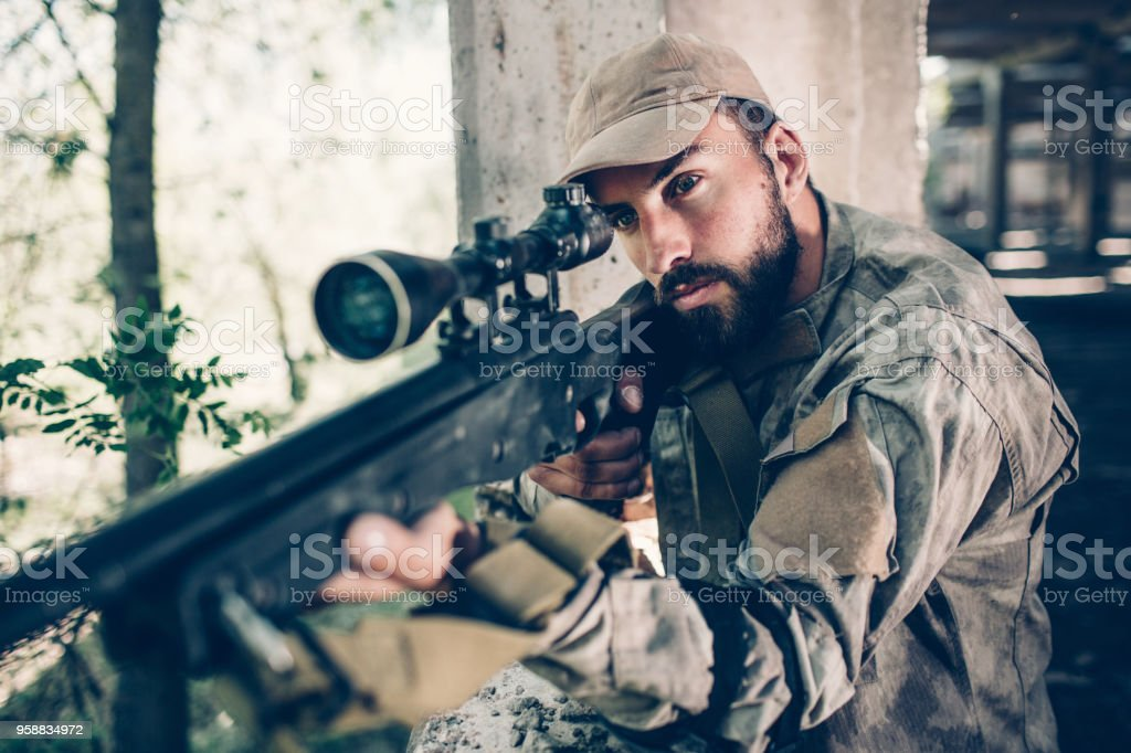 Serious and courage warrior is standing near open exit from hangar and looking though lens. He is taking aim using rifle. Bearded guy is concentrated. He is waiting stock photo