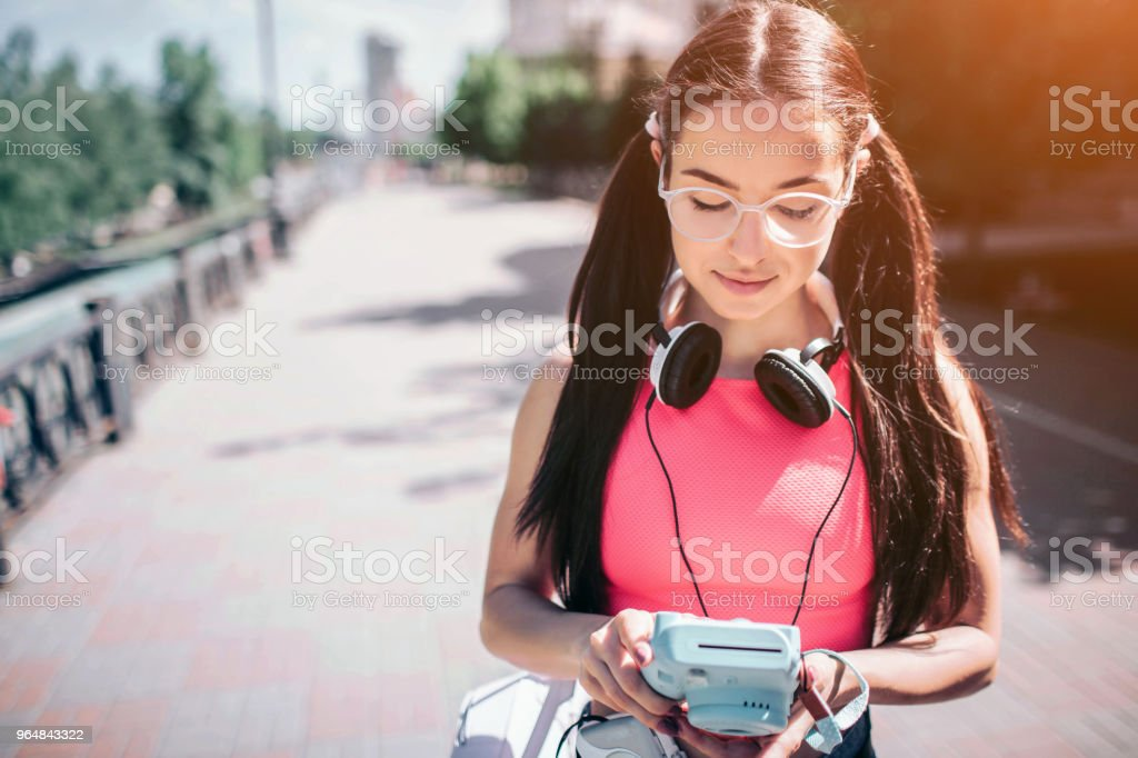 Serious and thoughtful girl is standing outside on street and looking on her music player. She wears glasses. Also there are headphones around girl's neck royalty-free stock photo
