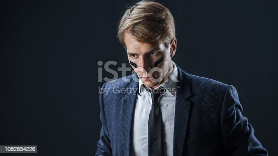 istock Serious and thoughtful young man in a business suit with war paint on his face 1082834226