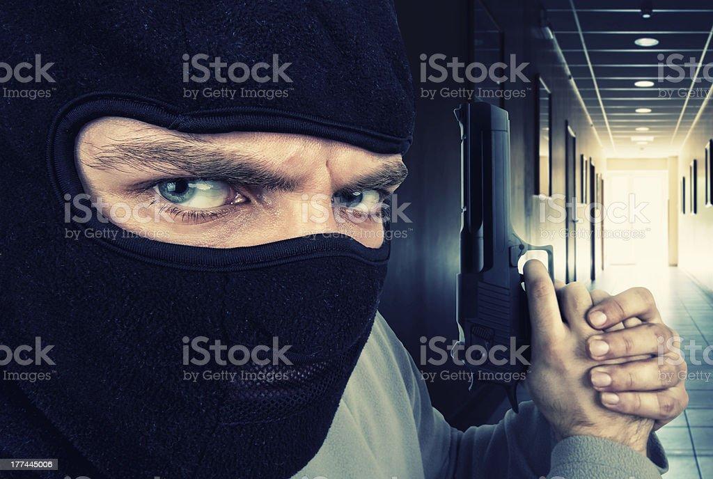 Serious armed criminal with gun stock photo