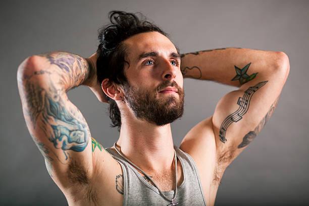 ernst arme hoch tattooed mann - musiknoten tattoos stock-fotos und bilder