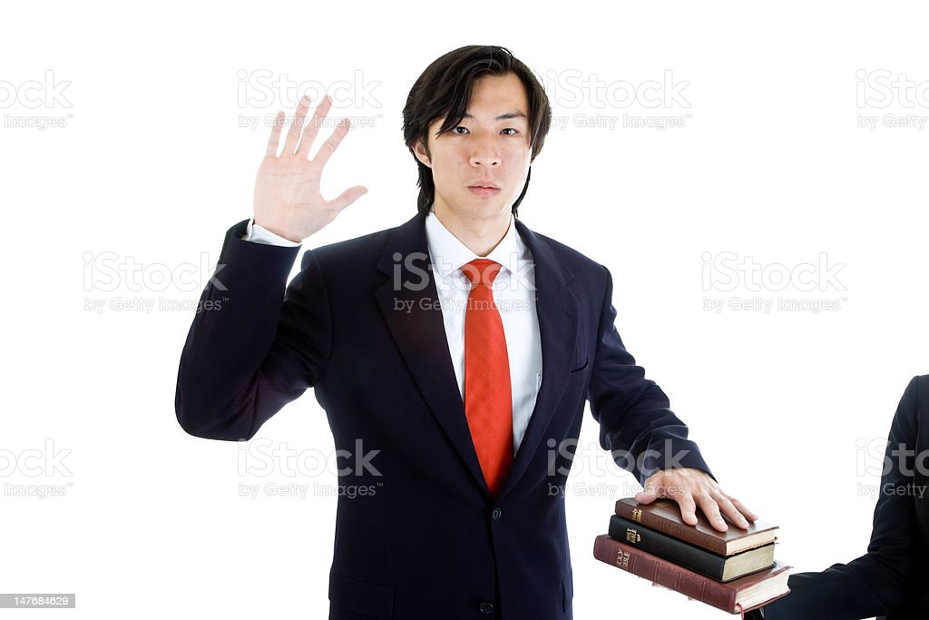 Serious Asian Business Man Swearing on Stack of Bibles, Isolated royalty-free stock photo