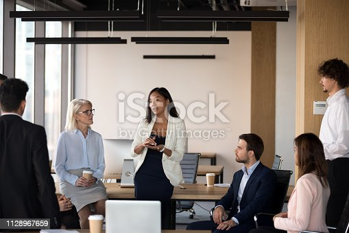 1085713886 istock photo Serious asian coach speaking at diverse corporate group meeting 1128967659