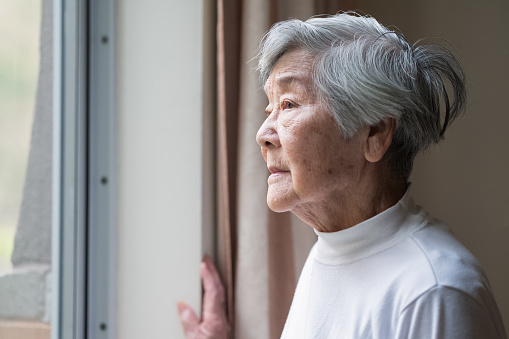 Chinese senior woman looking outside.