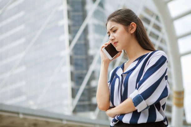 Serious asian young business woman talking on mobile phone in urban city . outdoor. stock photo