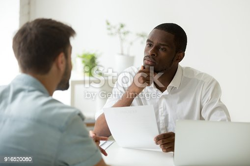 istock Serious attentive african hr listening to candidate at job interview 916520080
