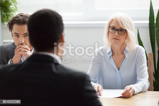 istock Serious attentive senior hr listening to candidate at job interview 924520290