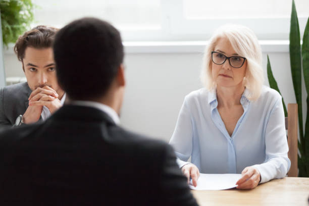 Serious attentive senior hr listening to candidate at job interview stock photo