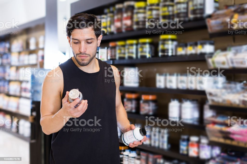 Serious attractive muscular guy holding sport nutrition stock photo