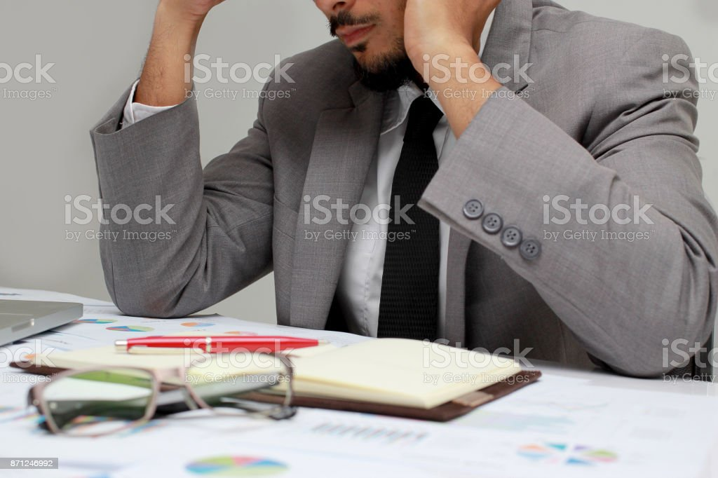 Serious attractive young handsome businessman sitting at desk in office busy talking on phone and working with laptop, notebook, pen, document at desk in the modern office,  keeping hands on his face. stock photo