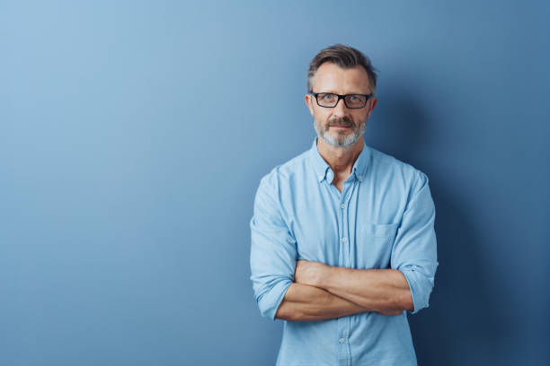 Serious authoritative man with folded arms stock photo
