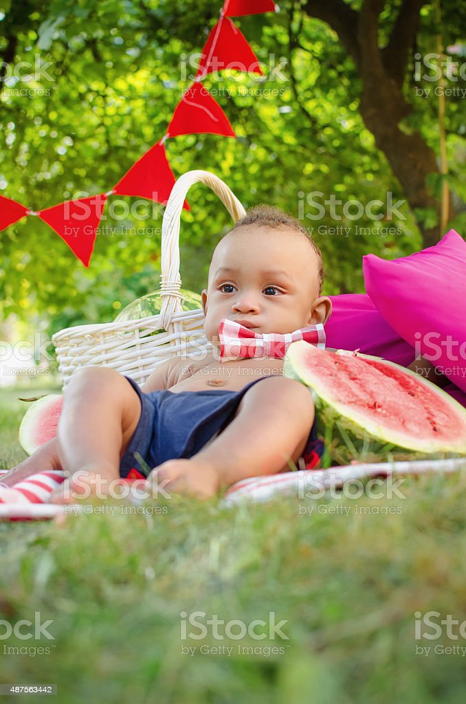 serious baby boy and watermelon stock photo