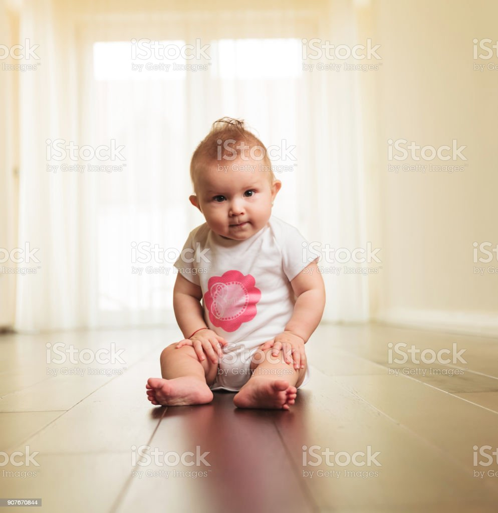 serious baby girl sitting on the floor stock photo