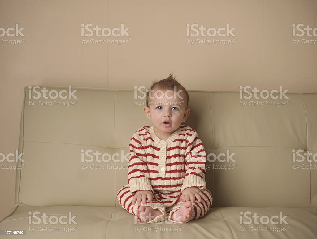 Serious Baby Sitting on Couch Wearing Pajamas royalty-free stock photo