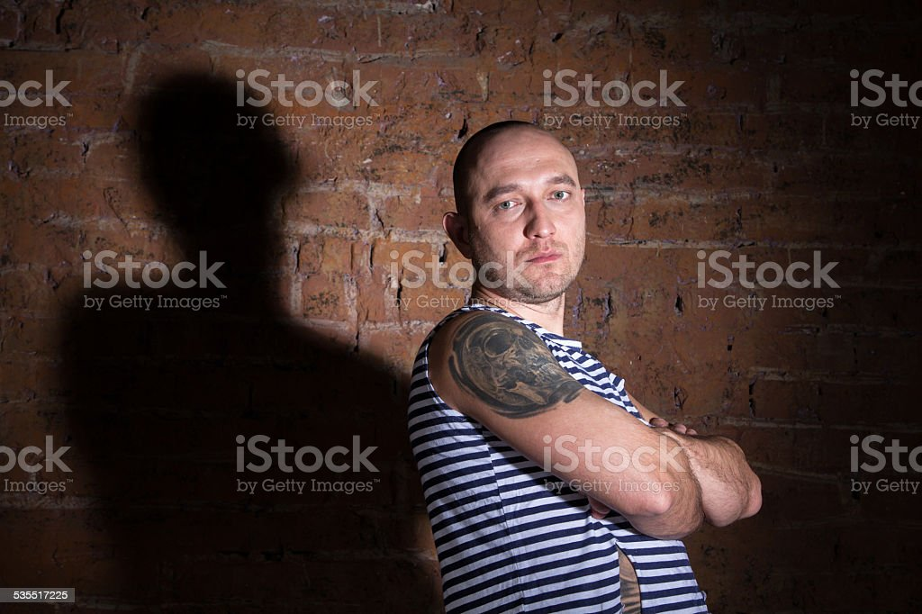 Serious bald man with tattoo standing near the brick wall stock photo