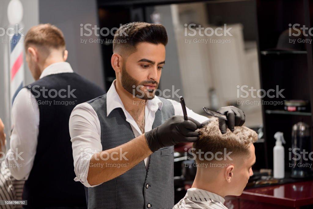 Serious Barber Making Stylish Haircut Using Comb And Razor Stock