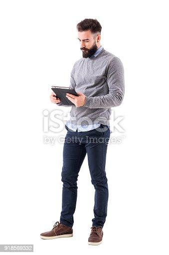 istock Serious bearded businessman or teacher reading notebook paper. 918569332