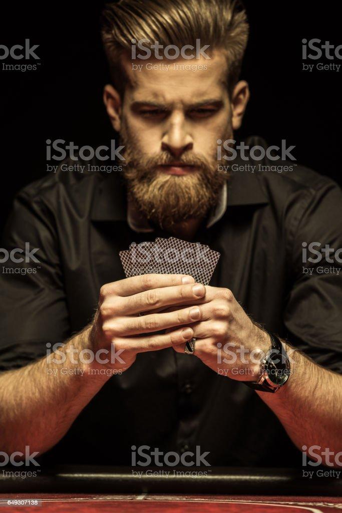Serious bearded man holding poker cards on black stock photo
