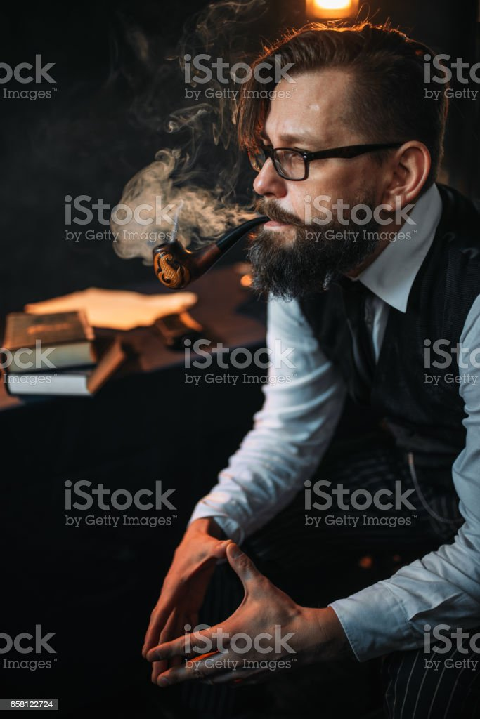 Serious bearded man in glasses smoking pipe royalty-free stock photo