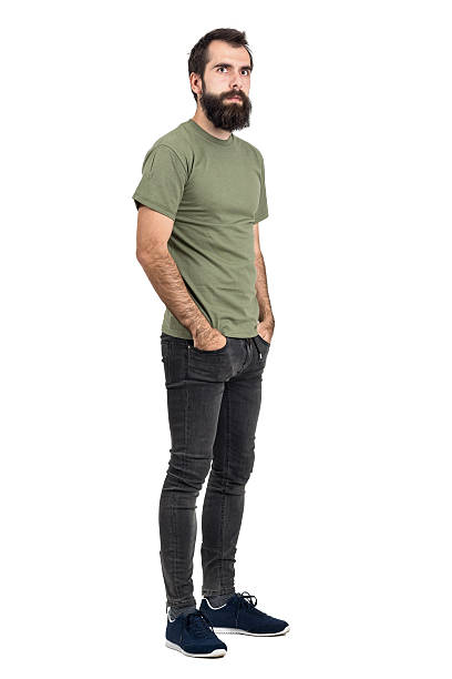 Serious bearded man with hands in pockets looking at camera Serious bearded man with hands in pockets looking at camera. Full body length portrait isolated over white studio background. men in tight jeans stock pictures, royalty-free photos & images