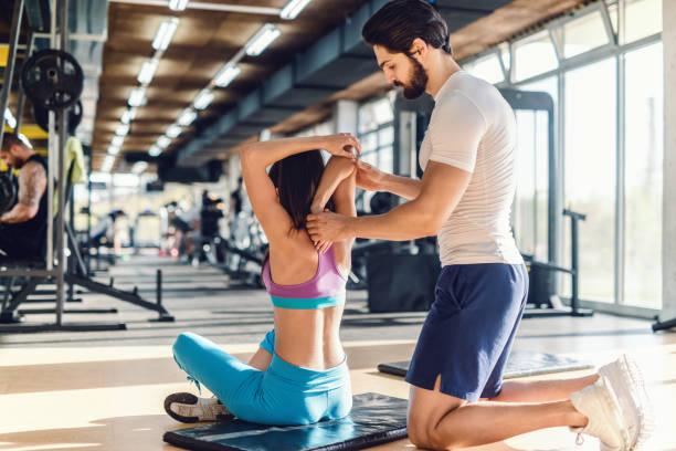 serious bebaarde persoonlijke trainer vrouw te strekken van de armen te helpen. de vrouw zit op de mat, sportschool interieur. - personal trainer stockfoto's en -beelden