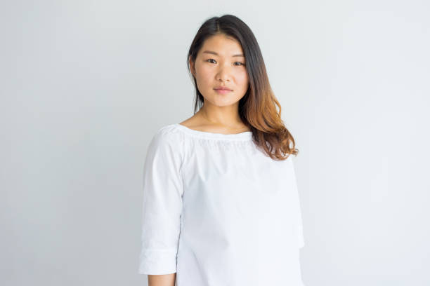 Serious beautiful young Chinese woman in white blouse Serious beautiful young Chinese woman in white blouse looking at camera. Portrait of calm confident girl with beautiful hair. Lady concept southeast asian ethnicity stock pictures, royalty-free photos & images