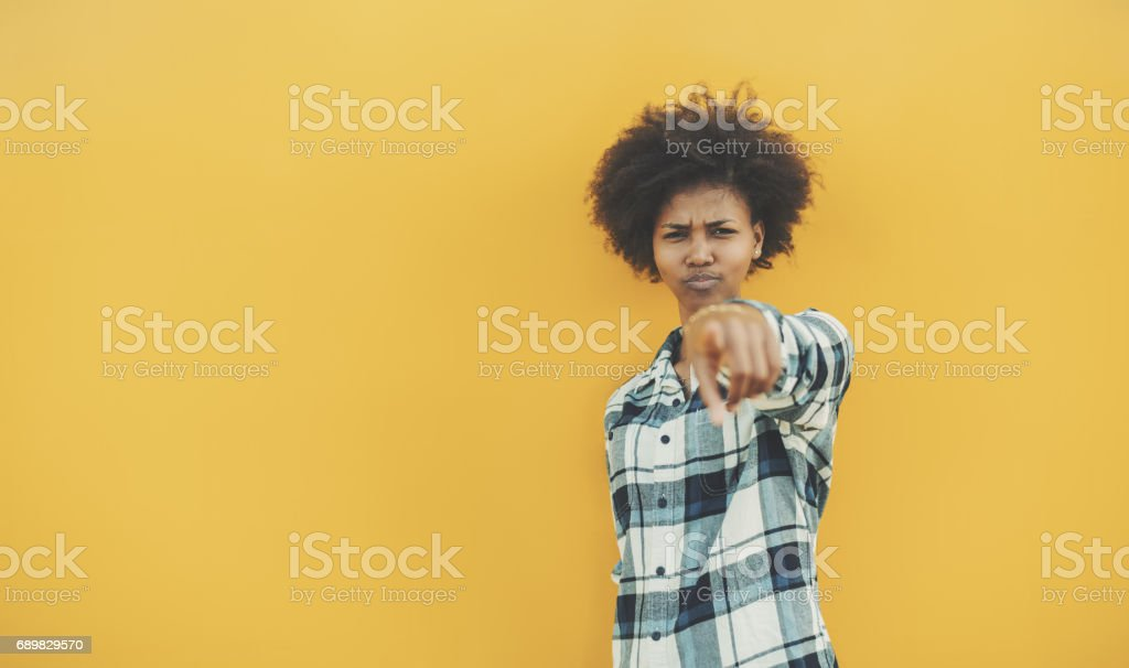 Serious black girl pointing on camera near yellow wall stock photo