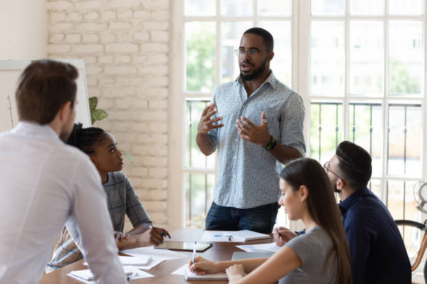 Serious black manager talk to diverse staff people at meeting stock photo
