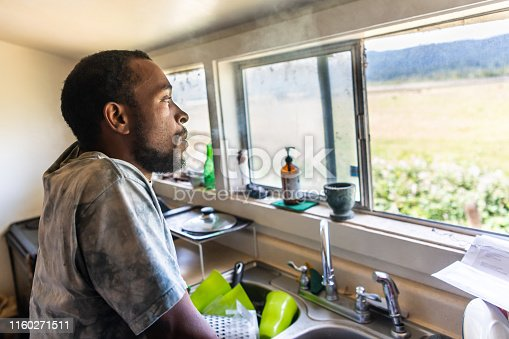 Serious afro caribbean mid adult man looking through a window at his home kitchen