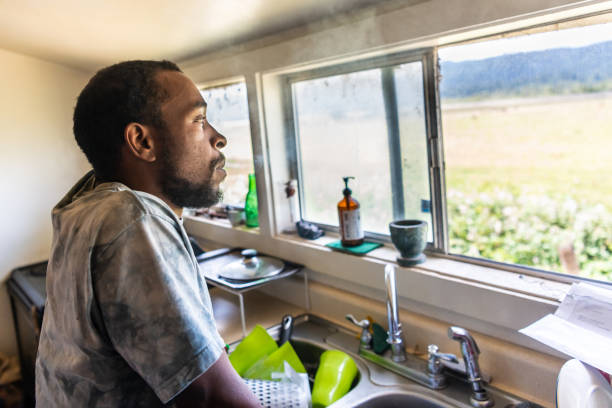 Serious black mid adult man looking through a window Serious afro caribbean mid adult man looking through a window at his home kitchen afro caribbean ethnicity stock pictures, royalty-free photos & images
