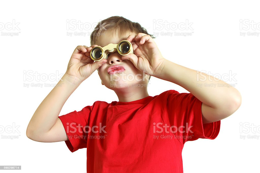 Serious boy in shirt looking through binoculars royaltyfri bildbanksbilder