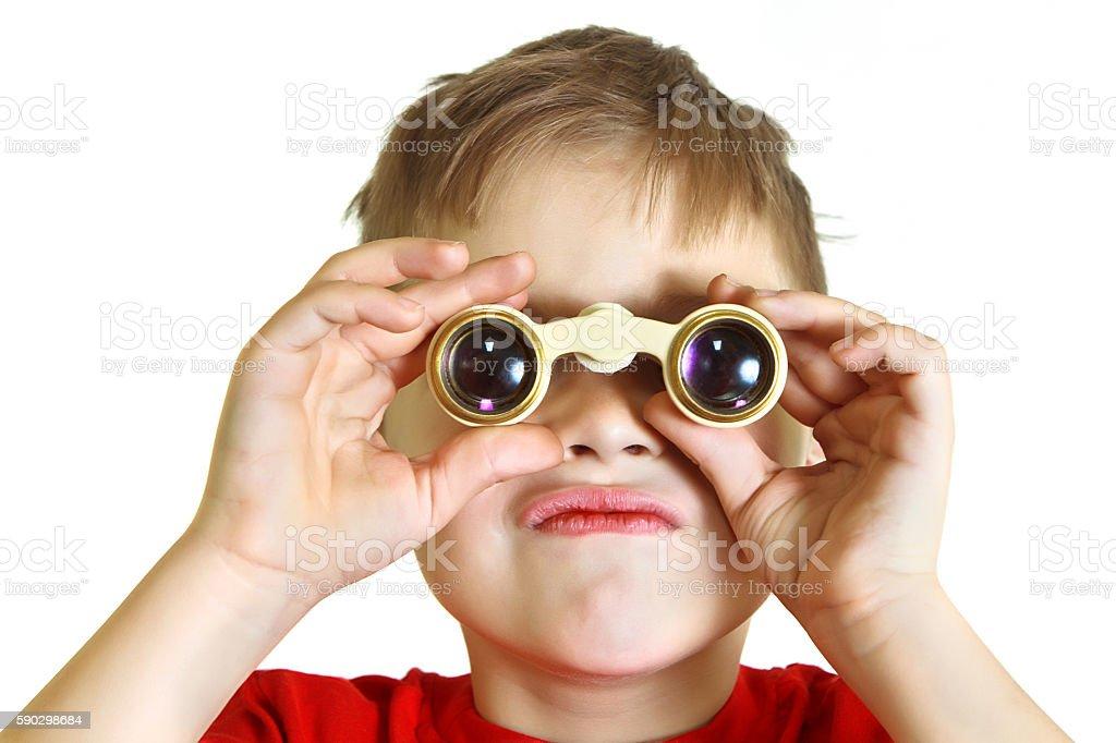 Serious boy looking through binoculars royaltyfri bildbanksbilder