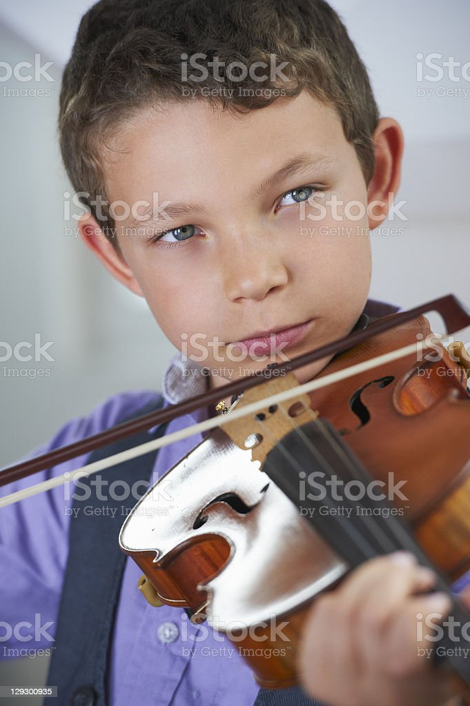Serious boy playing violin stock photo