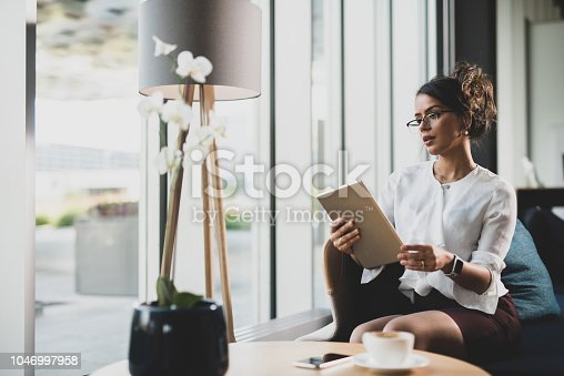 912944158istockphoto Serious Brazilian woman using iPad. 1046997958