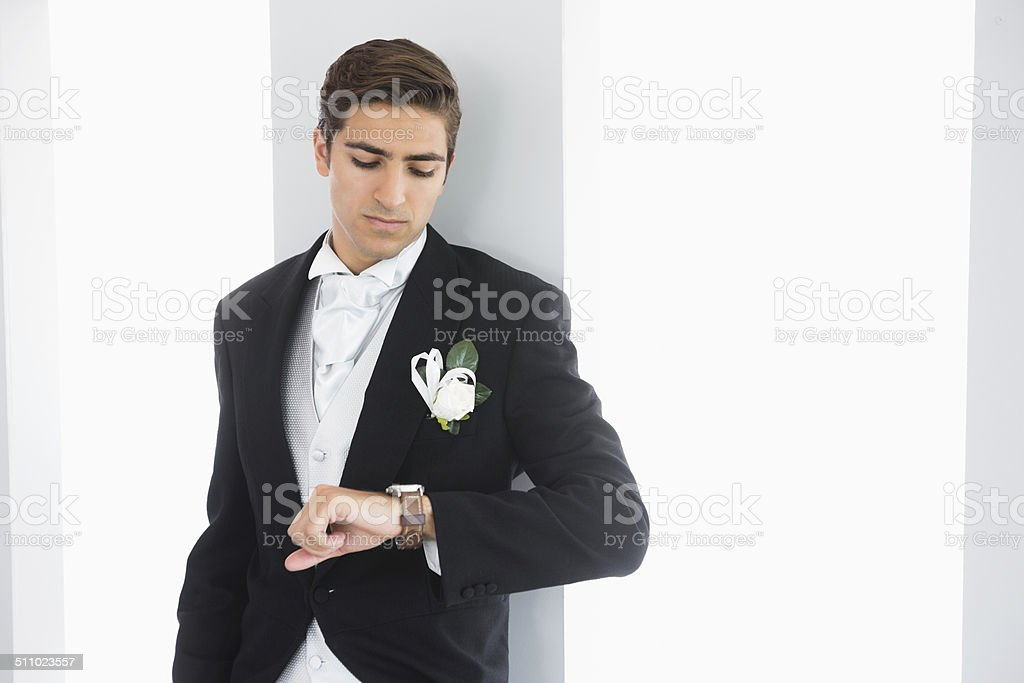 Serious bridegroom leaning against wall stock photo