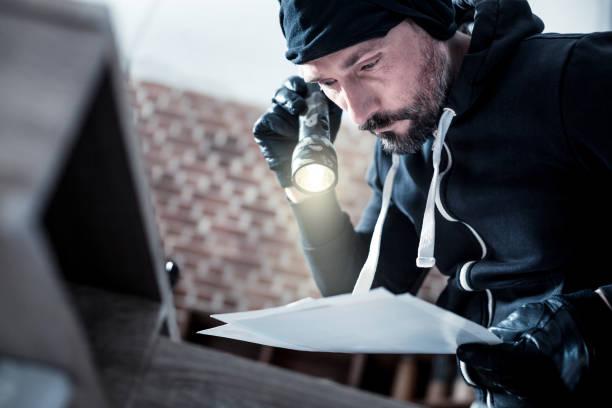 Ladrão séria lendo alguns documentos - foto de acervo