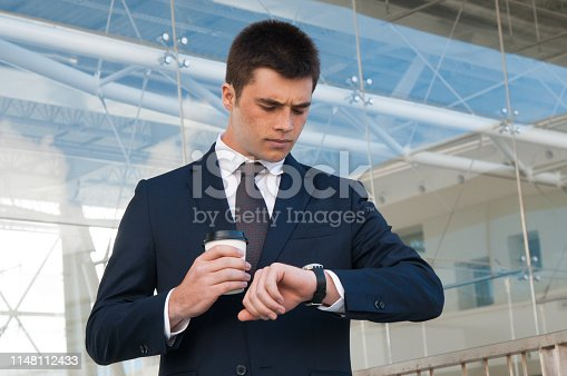 Serious business man checking time on watch outdoors. Handsome guy holding plastic coffee cup and standing with building glass wall in background. Business appointment concept. Front view.