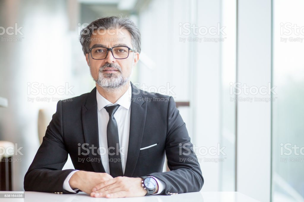 Serious Business Man Sitting at Empty Office Desk stock photo