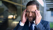 istock Serious business man suffering from migraine, headache disorder, symptoms 1091529574