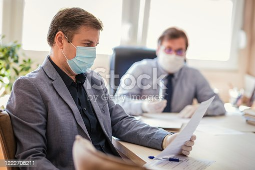 Two entrepreneurs sharing an office in times of corona disease, revising paperwork while wearing protective masks and gloves
