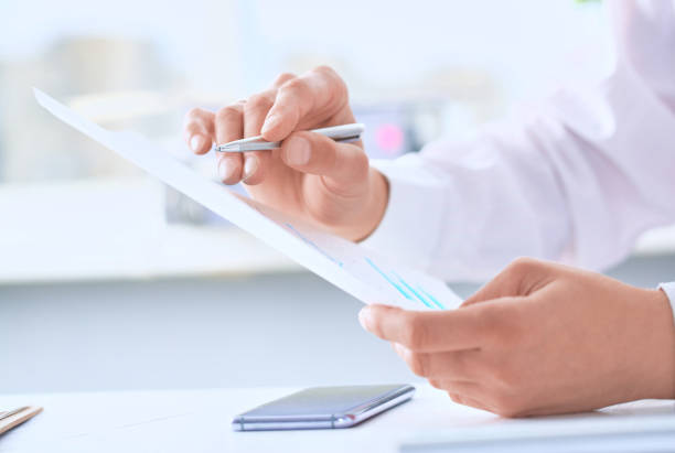 Serious business man working on documents and makes notes with a pen close-up. stock photo