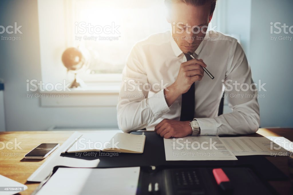 Serious business man working on documents Serious business man working on documents looking concentrated with briefcase and phone on the table 2015 Stock Photo