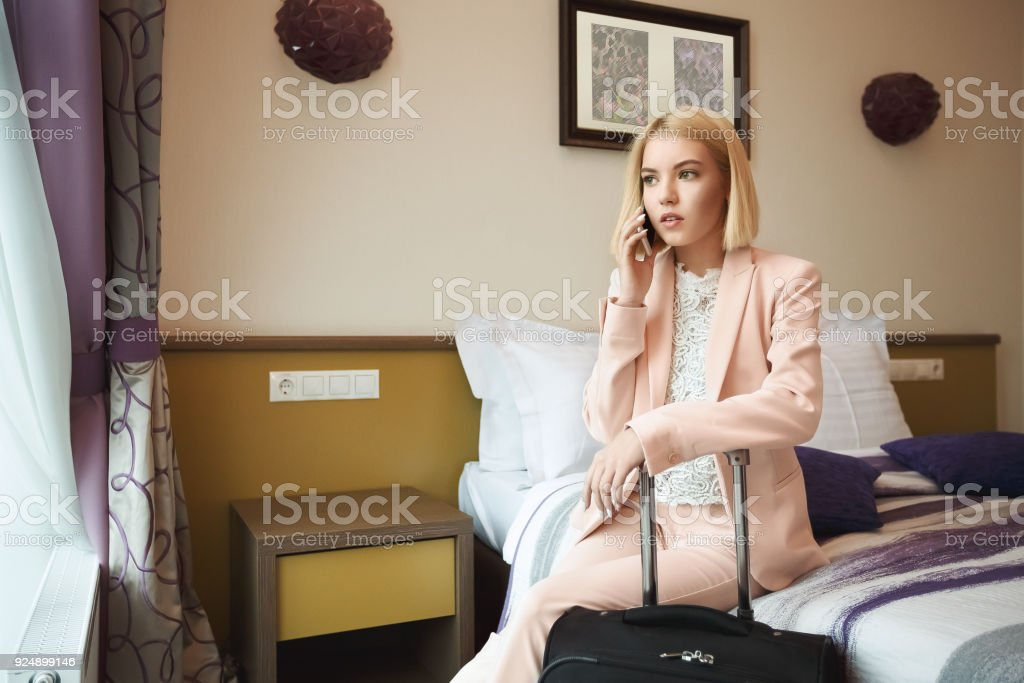 Serious business woman at the hotel room with suitcase, sitting on...
