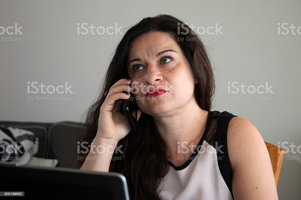 Serious business woman talking on her phone at home office stock photo