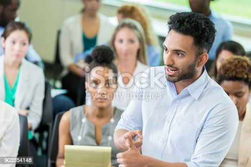 istock Serious businessman asks question during conference 903354148