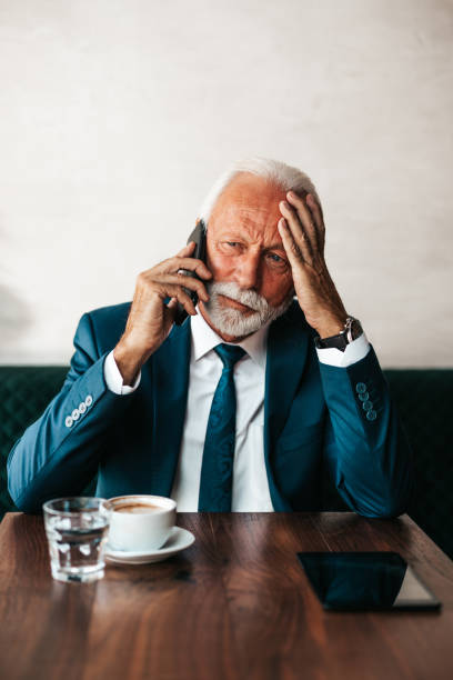 Serious businessman at restaurant table Handsome and elegant senior businessman sitting at restaurant table and drinking fresh espresso coffee. He is serious while using his smart phone to talk with someone. old man working in a pub stock pictures, royalty-free photos & images