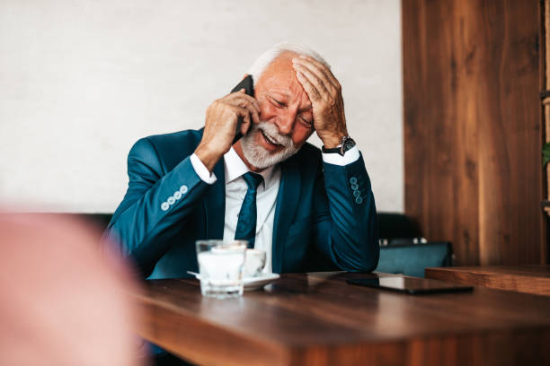 Serious businessman at restaurant table Handsome and elegant senior businessman sitting at restaurant table and drinking fresh espresso coffee. He is happy while using his smart phone to talk with someone. old man working in a pub stock pictures, royalty-free photos & images
